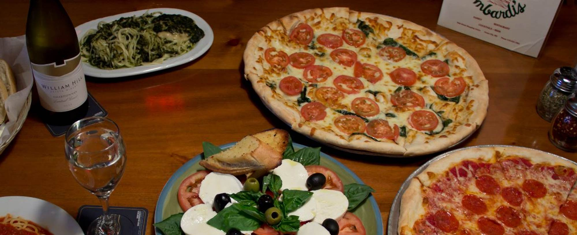 Two Pizzas Past And Italian Salad On Table With Wine At Lombardi S Pizza Ocmd